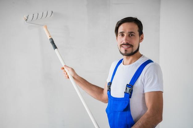 Ein arbeiter in einem blauen overall hält eine walze in den händen, lächelt und schaut in die kamera