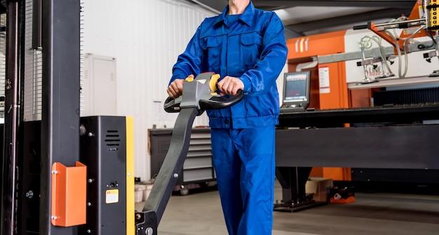 Ein arbeiter in einem lager verwendet einen handpalettenstapler, um paletten zu transportieren.