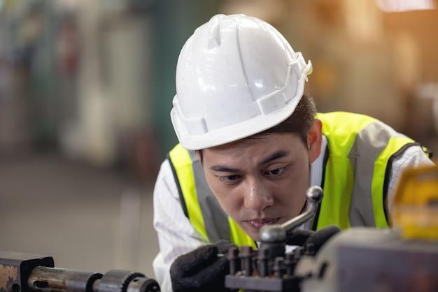 Ein arbeiter in gläsern steht in der nähe von industrieanlagen und überprüft die produktion. mensch bedienende maschine in der fabrik