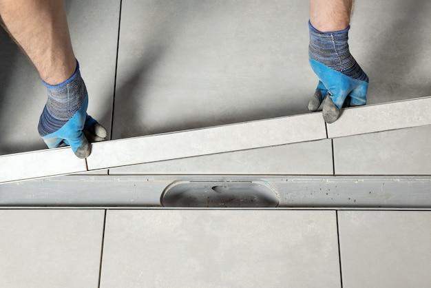 Ein arbeiter installiert im badezimmer einen mit keramikfliesen verzierten abflussdeckel