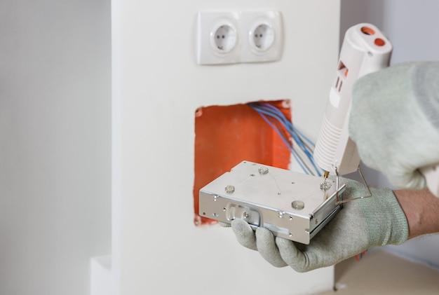Ein arbeiter installiert und verbindet die stromversorgung der led-hintergrundbeleuchtung.