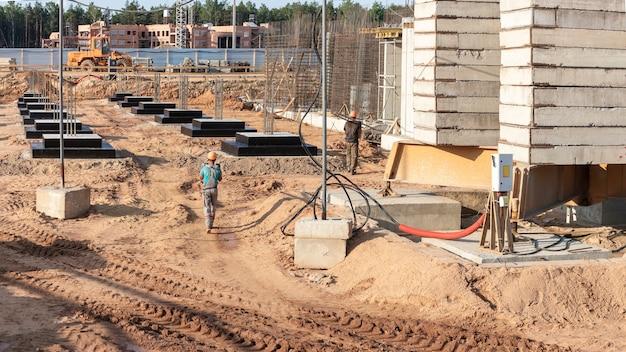 Ein arbeiter transferiert elemente für den einbau der schalung auf der baustelle. monolithische betonschalung beim bau eines wohnhauses.