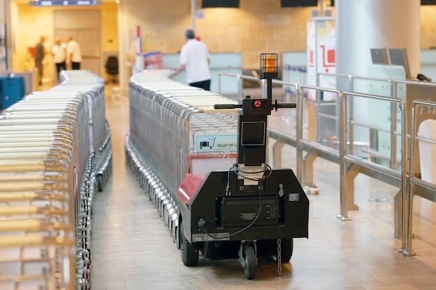 Ein arbeiter transportiert am flughafen wagen für gepäck.