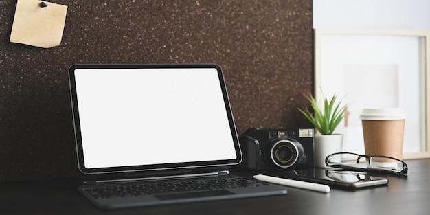 Ein arbeitsbereich ist von einem weißen computer-tablet mit leerem bildschirm und persönlicher ausrüstung umgeben.