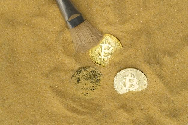 Ein archäologe räumt mit einem pinsel die bitcoin-münze auf der goldsand-mining-kryptowährung