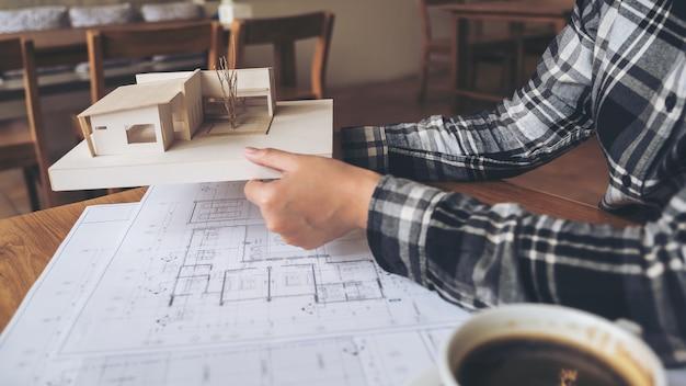 Ein architekt, der an architekturmodell mit geschäftszeichenpapier auf tabelle hält und arbeitet