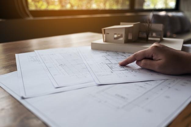 Ein architekt, der an einem architekturmodell mit geschäftszeichenpapier auf tabelle arbeitet
