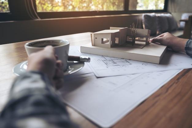 Ein architekt, der an einem architekturmodell mit geschäftszeichenpapier beim trinken von coffe arbeitet