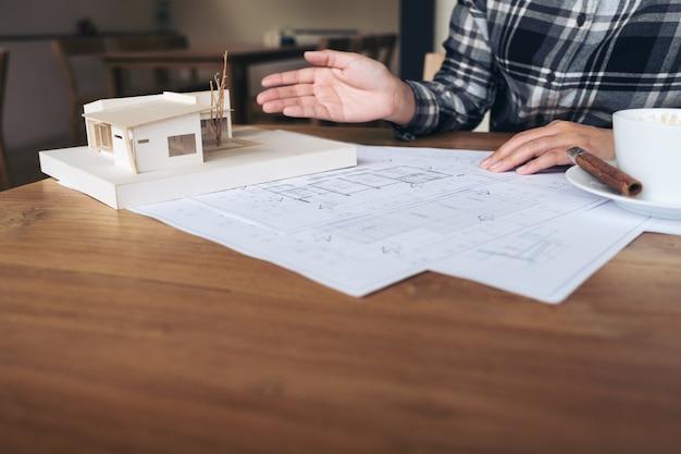 Ein architekt, der an einem architekturmodell mit geschäftszeichenpapier und kaffeetasse arbeitet