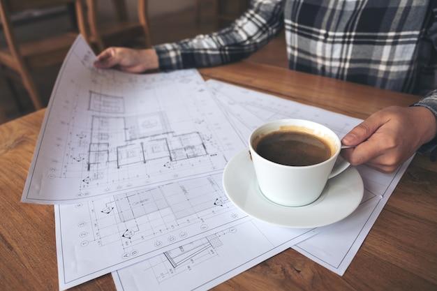 Ein architekt, der an geschäftszeichnungspapier beim trinken des kaffees im büro arbeitet