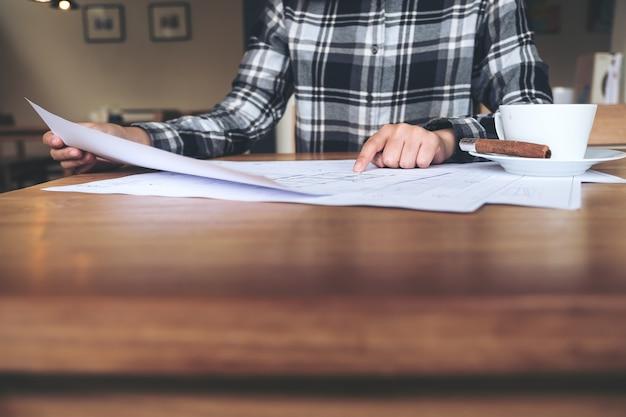 Ein architekt, der auf geschäftszeichenpapier auf tabelle arbeitet und zeigt