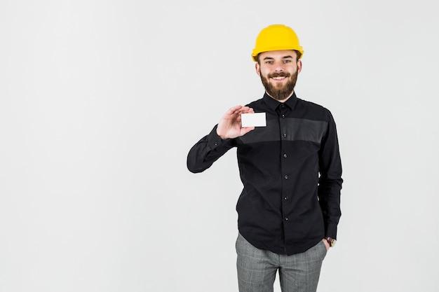 Ein architekt, der den hardhat zeigt visitenkarte gegen weißen hintergrund trägt