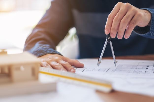 Ein architekt mit kompass zum zeichnen und messen von werkstattzeichnungen im büro