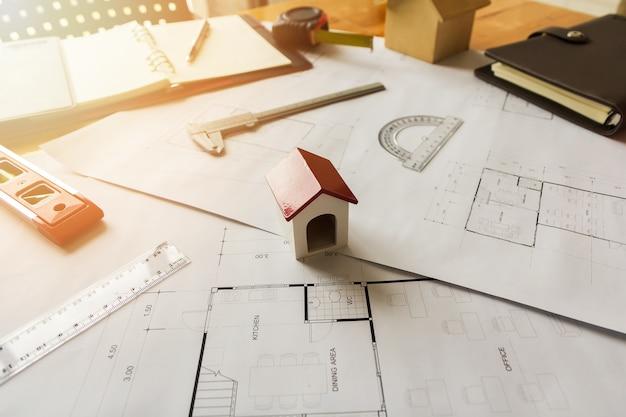 Ein architektenhausmodell mit plan und lichtpausen auf architektenschreibtisch.