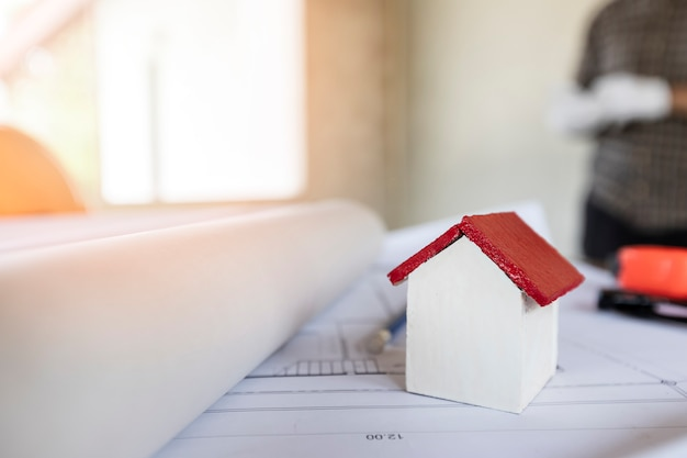 Ein architektenhausmodell mit plan und plänen auf architektenschreibtisch