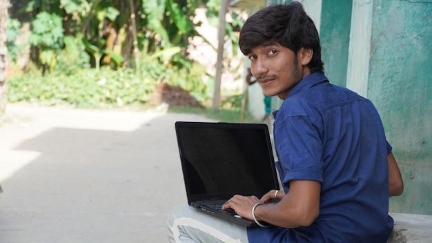 Ein armer junge mit laptop besucht den online-unterricht im dorf