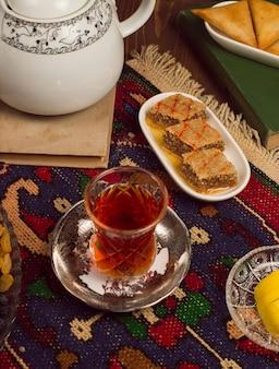 Ein armudu traditionelles glas tee mit bonbons und sheki pakhlavasi auf dunkelheit