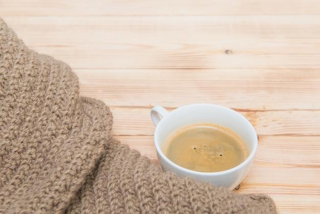 Ein aromatassekaffee mit gemütlichem gestricktem schal auf holztisch. trinken, kaffee, hygge-thema