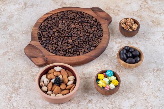 Ein arrangement aus kaffeebohnen, glasierten erdnüssen, süßigkeiten und verschiedenen nüssen