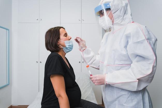 Ein arzt, der eine pcr durchführt, um covid 19 an einer schwangeren frau in der arztpraxis nachzuweisen