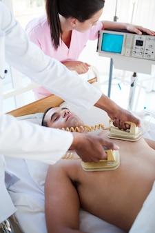 Ein arzt, der einen patienten mit einem defibrillator wiederbelebt