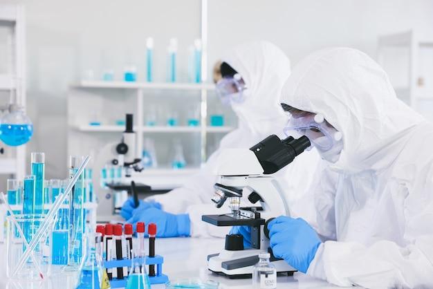Ein arzt in einem anzug gegen die pest ist vollständig vor dem virus geschützt. er trägt sterile gummihandschuhe und schaut durch die linse eines mikroskops, während er in einem labor sitzt.