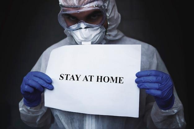 Ein arzt in einem biochemischen schutzanzug und einer maske mit einem papier mit aufschrift bleibt zu hause auf einem dunkelschwarzen hintergrund. schutz vor coronavirus- oder covid-19-epidemie