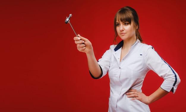 Ein arzt in einem weißen kittel hält einen neurologischen hammer auf rotem grund, um reflexe zu testen