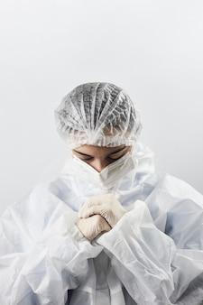 Ein arzt in schutzkleidung betet. krankenschwestern stehen auf, um zu beten. covid combat fatigue. gesundheitsvorsorge