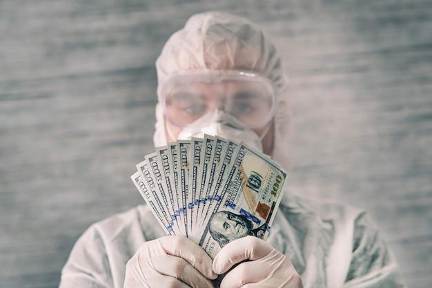 Ein arzt in schutzuniform hält geldscheine in den händen. bezahlung für die arbeit des arztes. die gefahr von keimen auf bargeld. desinfektion von papiergeld.