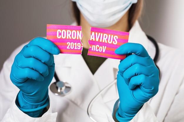 Ein arzt riss ein blatt papier mit der aufschrift coronavirus auf