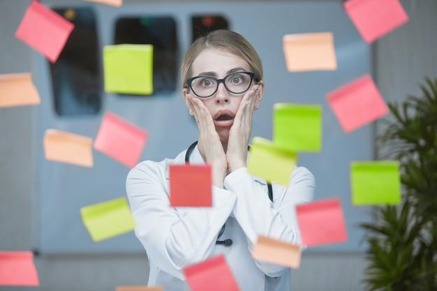 Ein arztmädchen posiert vor einem hintergrund von bunten aufklebern, die auf ein transparentes glas geklebt sind