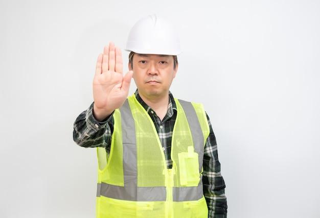 Ein asiatischer arbeiter mittleren alters, der die hand hebt und seine ablehnung ausdrückt.