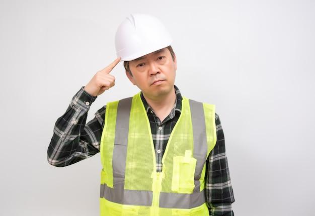 Ein asiatischer arbeiter mittleren alters, der sorgfältig über etwas nachdenkt.