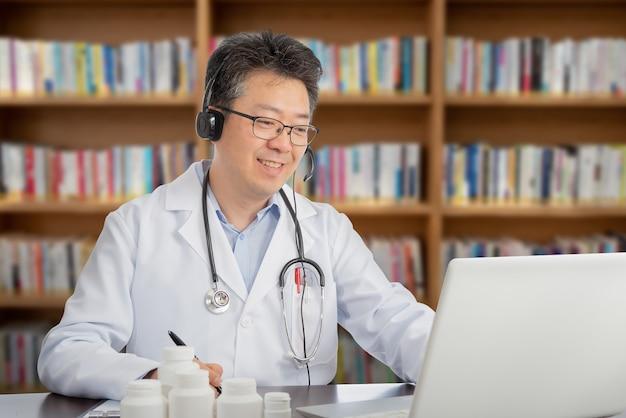 Ein asiatischer arzt, der sich mit einem patienten aus der ferne berät. telemedizin-konzept.