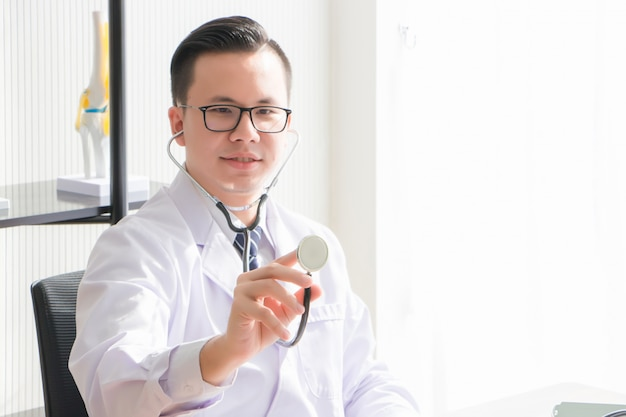 Ein asiatischer arzt, thai, trägt eine brille und eine uniform. der arzt sitzt, hält und hält das stethoskop im untersuchungsraum
