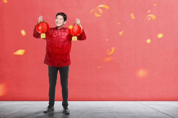Ein asiatischer chinesischer mann in einem cheongsam kleid, das chinesische laterne anhält