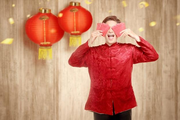 Ein asiatischer chinesischer mann in einem cheongsam kleid, das rote umschläge anhält
