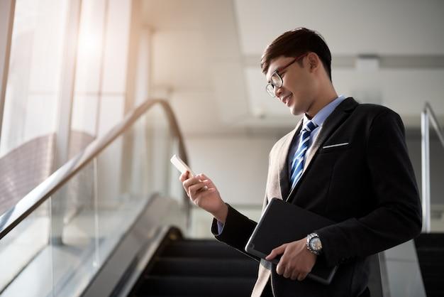 Ein asiatischer geschäftsmann, der sein laptop-tablett, geschäftskonzept hält.