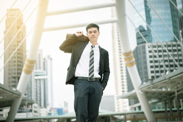 Ein asiatischer geschäftsmann wird arbeiten. er ist in der hauptverkehrszeit. sein büro befindet sich in bangkok.
