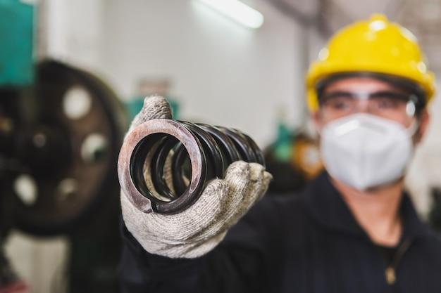 Ein asiatischer männlicher arbeiter überprüft die qualität des metallteils anhand der metallarbeiten in der fabrik. die herstellung von metallteilen und die überprüfung der qualität.