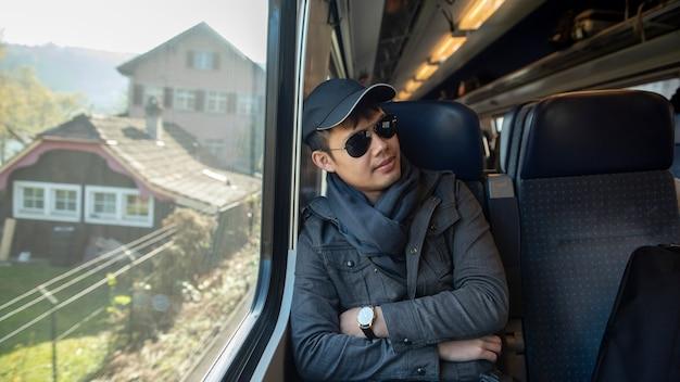 Ein asiatischer mann, der mit der eisenbahn in europa reist