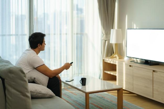 Ein asiatischer mann hält eine fernseh-fernbedienung in der hand und drückt auf den kanal, während er zu hause auf der couch im wohnzimmer fernsieht.