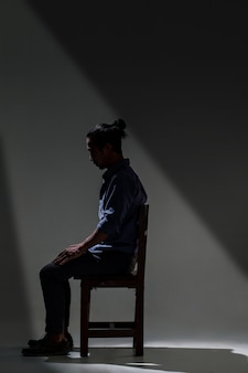Ein asiatischer mann leidet unter depressionen in der dunkelheit.