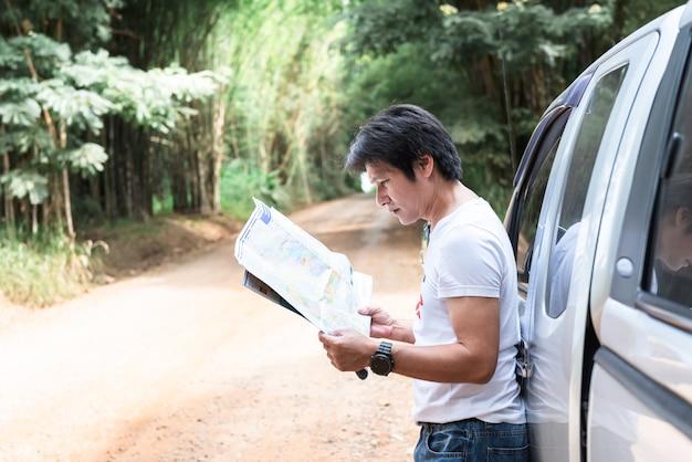 Ein asiatischer mann mittleren alters tourist, der in der nähe eines pickup-lastwagens steht, geparkt entlang der straße und blick auf eine karte, um wegbeschreibungen für die reiseplanung zu personen und transportkonzept anzuzeigen.