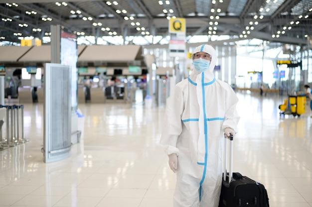 Ein asiatischer mann trägt einen ppe-anzug auf dem internationalen flughafen, sicherheitsreisen, covid-19-schutz und soziales distanzierungskonzept.
