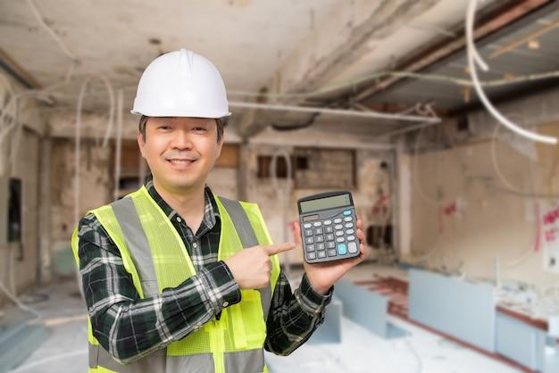 Ein asiatischer mann von mittlerem alter, der eine weiße arbeitskappe und einen arbeitsanzug hält einen taschenrechner in seiner hand trägt.