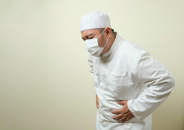 Ein asiatischer muslimischer fetter kerl mit maske, der schmerzen im magen hat, geste, die den magen hält