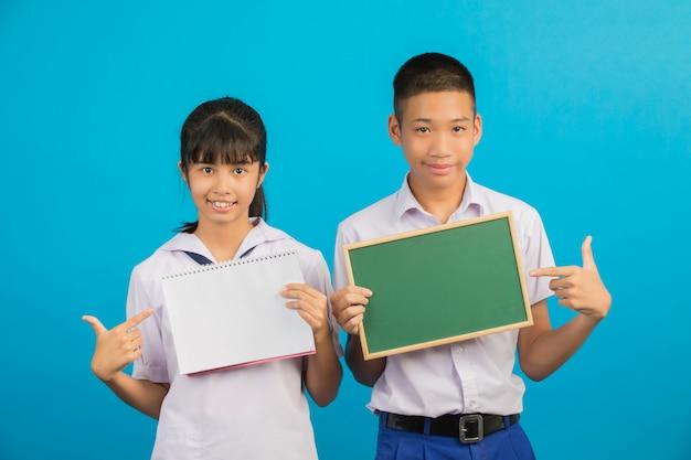 Ein asiatischer student, der ein notizbuch hält, und ein asiatischer männlicher student, der ein grünes brett auf einem blau hält.