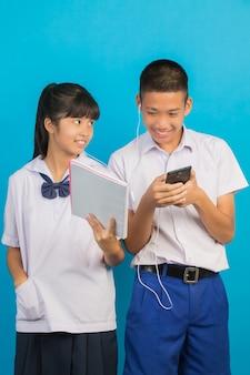 Ein asiatischer student, der ein notizbuch und einen asiatischen männlichen studenten stehen hält, spielend auf dem blau.